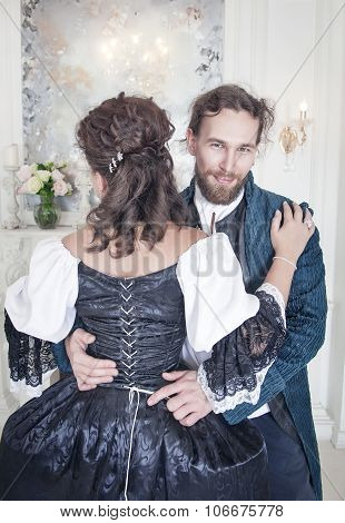 Handsome Man Untying Corset Of Woman In Medieval Dress