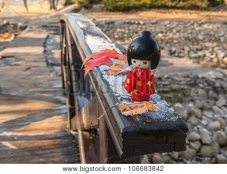Japanese  Doll Kokeshi On The Background Of Maple Leaves