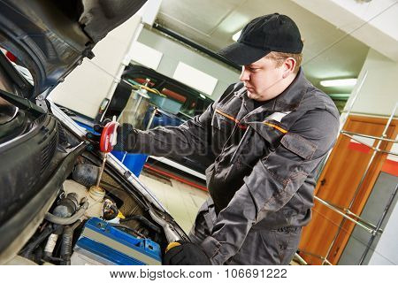 Car inspection. Automobile mechanic using a hydrometer areometer to check the concentration of antifreeze in the coolant at repair service station