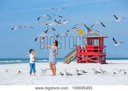 Young mother and her son feeding seagulls on tropical beach