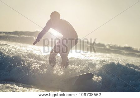 Surfer Getting On The Wave With His Board