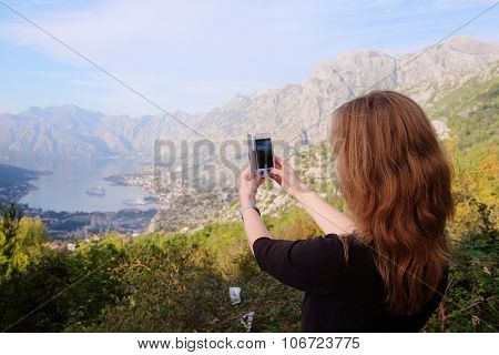 Girl tourist photographs a landscape with sea and mountains in Kotor, Montenegro