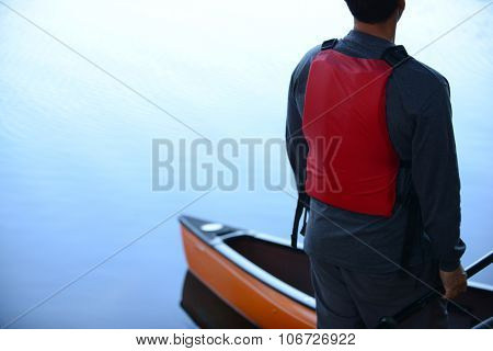 Man With Kayak On Calm Lake