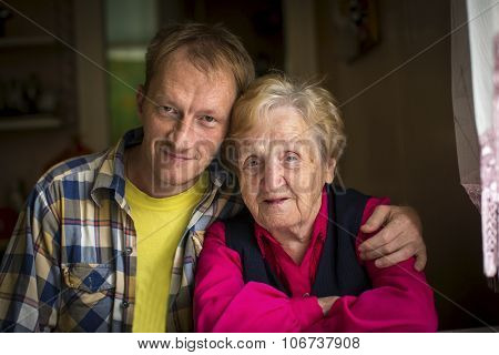 Portrait of an elderly woman with her adult grandson.