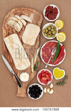 Italian antipasti selection with olives, salami, chilli peppers, sun dried and fresh tomatoes, garlic, lemon, oil, with ciabatta bread on an olive wood board on brown ridged paper  background.