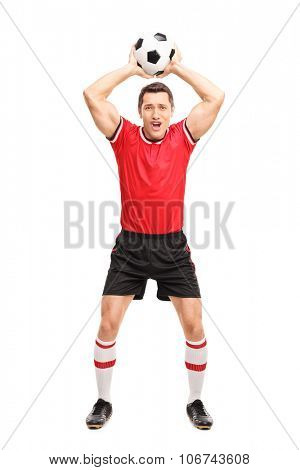 Full length portrait of a young football player taking a throw-in and looking at the camera isolated on white background