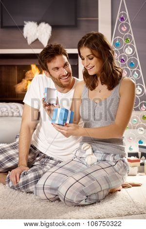 Young couple opening presents at christmas morning in pajamas on floor.