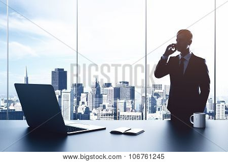 Businessman Talking On The Phone In The Office With Laptop On The Table