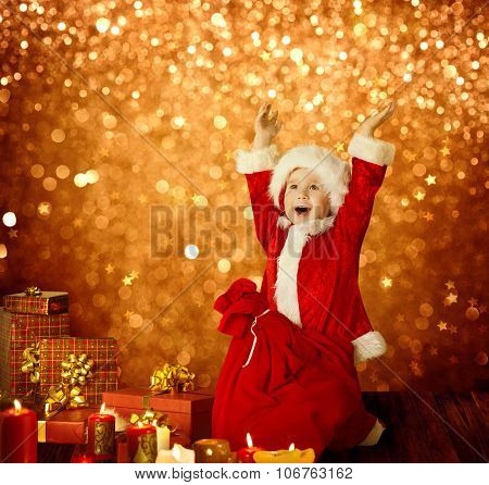Christmas Kid Happy Child Presents Gifts and Red Santa Bag Boy Arms up Golden Xmas Lights