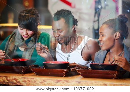 Man and women, black and Latin people, eating late in Korean eatery