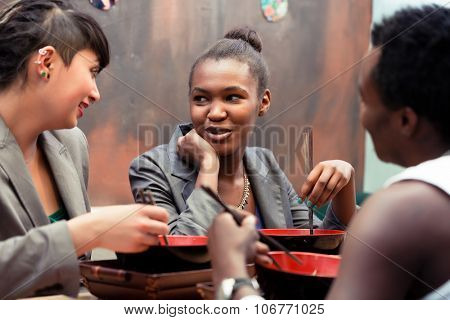 Friends, black and Latin people, eating ramen noodle soup in Japanese Restaurant poster