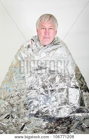 A lost hiker stays warm in an emergency Space Blanket while waiting for help