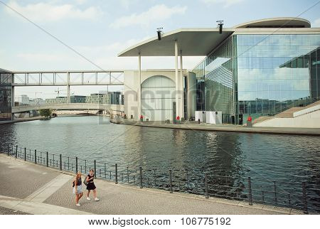 Women Walking Along Spree River And Buiding Of German Federal Chancellery
