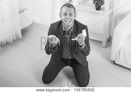 Young Male Businessman Anger, Hysterical Kneeling On The Floor, Screaming And Holding Crumpled Paper