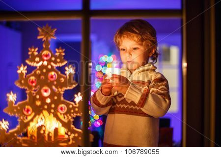Little Kid Boy Standing By Window At Christmas Time And Holding
