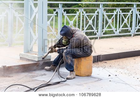 Worker In Protective Clothes Cleans The Metal Structures Sandblasting Tool
