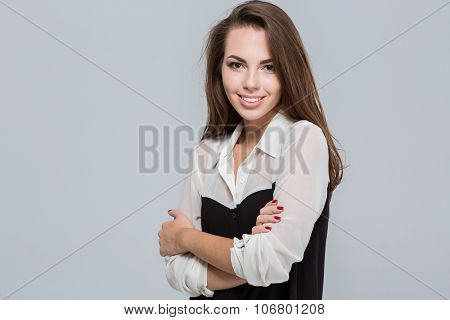 Portrait of a smiling young businesswoman standing with arms folded over gray background