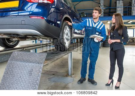 Dedicated and professional service mechanic, showing a customer around her car, which has just been serviced and equipped with winter tires. The mechanic is holding a cloth