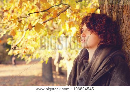 Young adult man portrait standing near the tree, oudoor in autumn park.