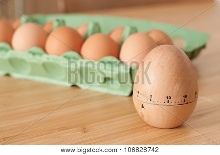 Timer with eggs and carton on the breakfast table poster