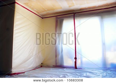 Room covered with clear plastic sheeting after asbestos abatement completed on popcorn ceiling poster
