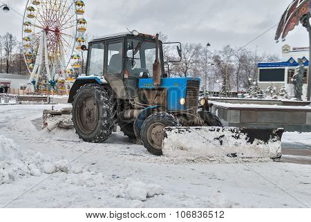 Tractor with snowplowing equipment cleans street