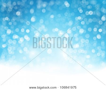 Abstract blue white background with blurry lights that give it a magical feeling as a backdrop for the Christmas season or any festive occasion.
