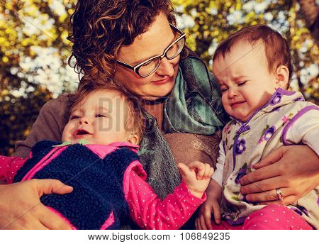 Tight Crop Of Mom Holding Crying Toddler Girls
