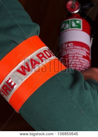 Fire warden with a reflective high visibility identification patch holding a fire extinguisher