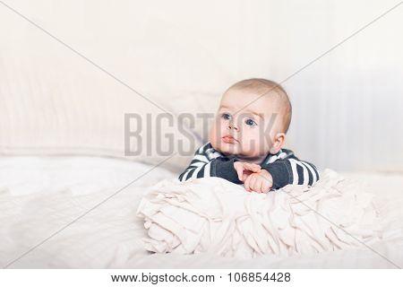 Cute happy baby boy with big blue eyes.