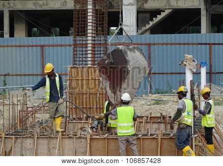 Construction workers pouring concrete slurry into ground beam formwork