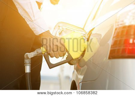 Close up business man pumping gasoline fuel in car at gas station, golden sunlight background.