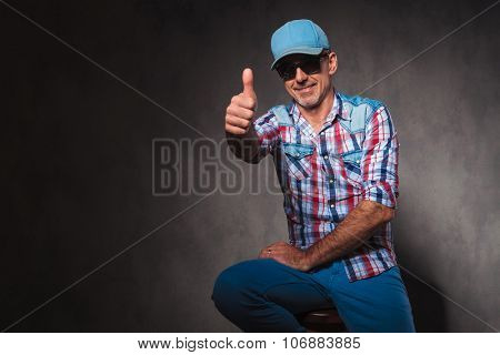 positive old casual man in trucker hat making the ok thumbs up hand sign while sitting in studio