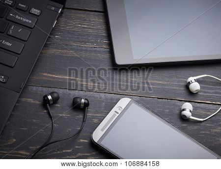 Laptop, smart phone, tablet pc and headset on wooden background