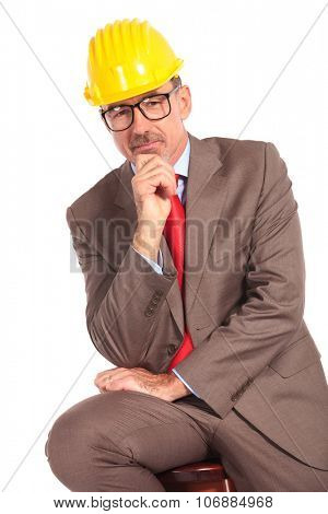 pensive old construcion engineer sitting on chair on white background