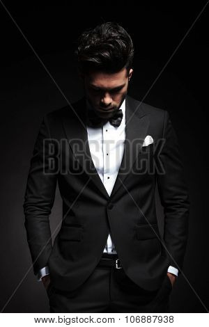 Portrait of a elegant young business man looking down while holding both hands in his pocket.