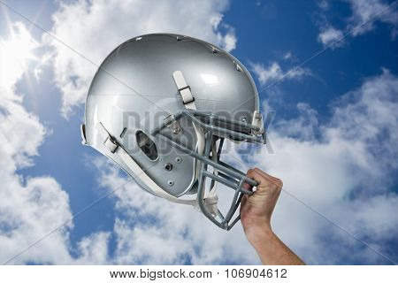 Close-up of American football player handing his sliver helmet against bright blue sky with clouds