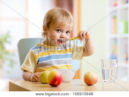 child eating healthy food with with the left hand at home