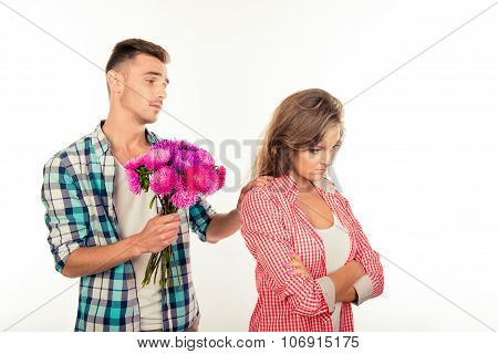 Handsome  Man Giving A Bouquet To His Beloved And Asking To Forgive Him