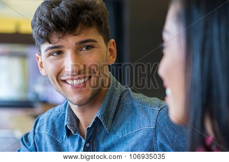 Portrait of happy young man looking his girlfriend and smiling. Couple loving eachother indoor. Shallow depth of field with focus on handsome young man smiling.