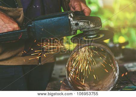 grinder man in workshop worker grinding steel pipe in workshop grinding sparks flying around retro toned image with selective focus poster