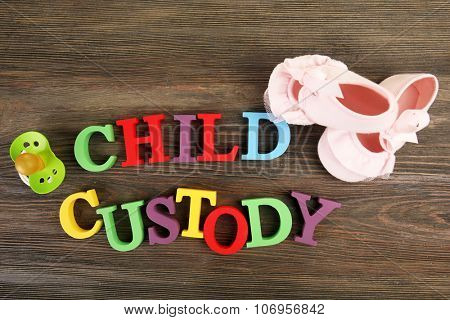 Baby's booties, dummy and colourful letters regarding child-custody and family-law concept