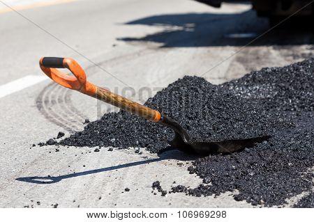Shovel For Road Construction Works In A Heap Of New Asphalt