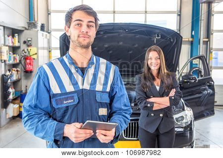 A proud, professional and skilled service mechanic, standing in front of a car and the owner of the car, confidently looking, he takes pride in his work