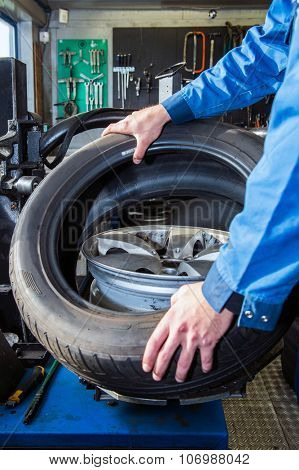Mechanic mounting a tire on a light weight alloy rim in a garage poster