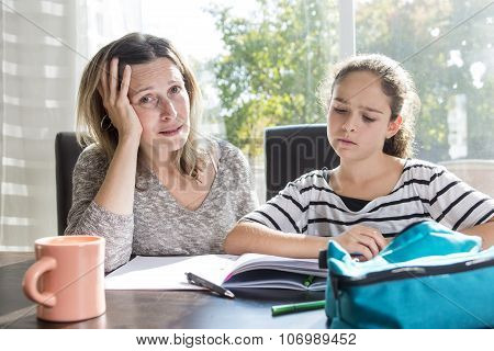 schoolgirl studying with books on the kitchen table