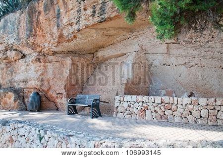 Bench under massive limestone rock