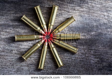 Macro shot of small-caliber tracer rounds with a red tip. Ammunition composition lie in Ida range, on the tops of bullets into the textural wooden background. poster