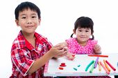 Little asian children playing and creating toys from play dough on table. Boy and girl smiling and looking at camera on white background. Strengthen the imagination of child poster