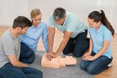 Mature Male Instructor Showing Cpr Training On Dummy To His Student poster
